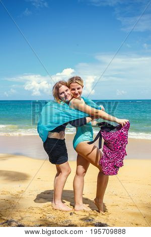two happy girls with pareos on the sandy beach on background of blue sky