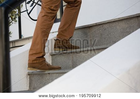 Low section of man moving up on staircase