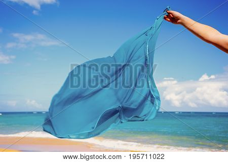 blue pareo shawls flowing in the wind on background of sea
