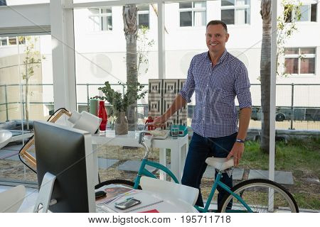 Portrait of smiling designer holding bicycle while standing by desk in office
