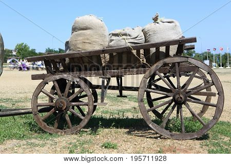 Horse-drawn carriage with bags of grain in the field