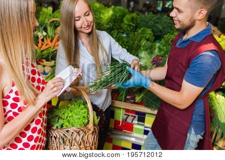 The seller and two girls with a basket of vegetables. Girlfriends buy vegetables on the market.