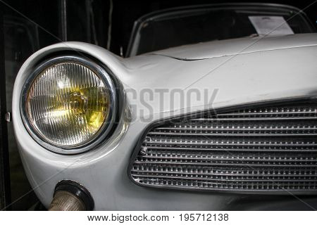 Poland, Otrebusy, 31 March 2017: Frond Close Up View On A Light Of Cool Old Car