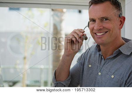 Portrait of smiling designer talking on microphone at office