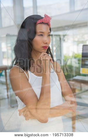 Thoughtful businesswoman looking through window at office seen through glass