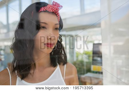 Thoughtful businesswoman looking through window at studio seen through glass