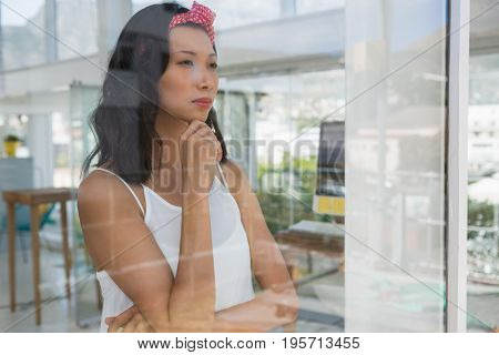 Thoughtful businesswoman looking through window seen through glass