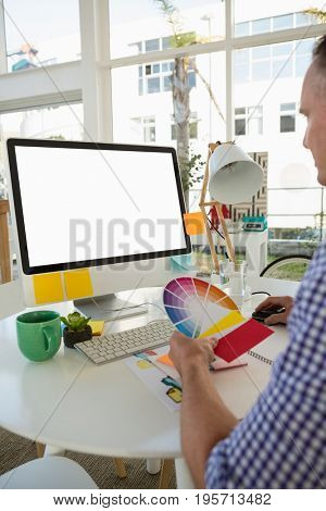 Designer holding color swatch while sitting at desk in office