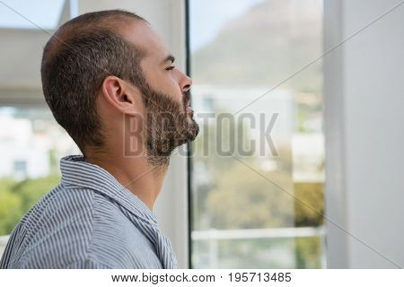 Thoughtful designer looking through window while standing at office