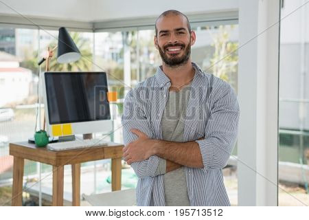 Portrait of smiling male designer with arms crossed standing in office