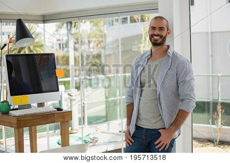Portrait of smiling male designer leaning by window on wall in office