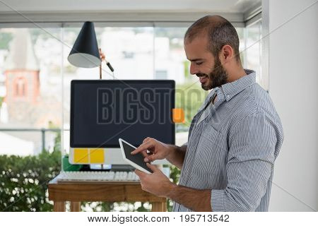 Side view of designer using digital tablet while leaning on wall at office