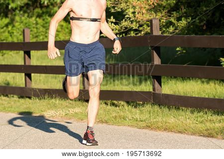 Man running on a sunny afternoon shirtless with a heart rate monitor strapped across his chest with trees and a fence behind him