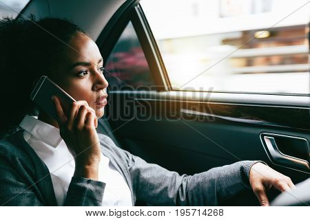 Young businesswoman talking on mobile phone, sitting on back seat of a car