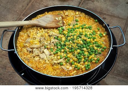 Peas And Sweetcorn Added To Chicken Paella In An Outdoor Pan