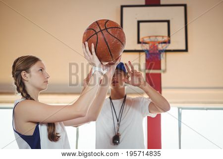 Coach advising female basketball player while practicing in court