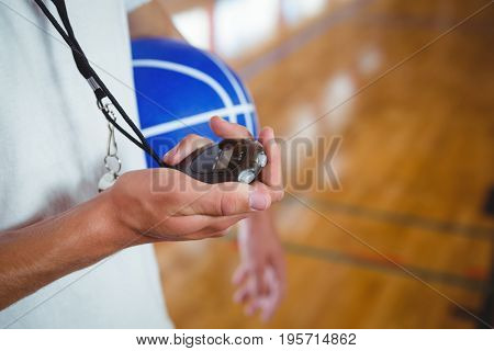 Midsection of basketball coach with stopwatch standing in court