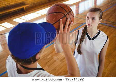 High angle view of male coach training female basketball player during practice in court