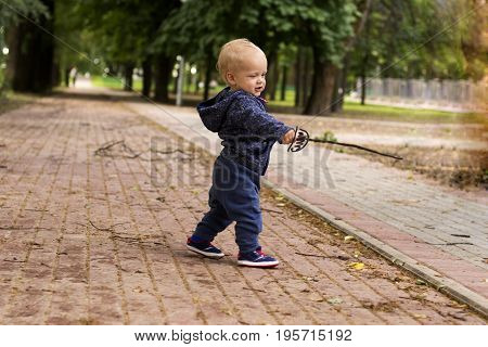 Cute toddler with a drawn rapier. Funny baby boy in the park with a pictured epee.