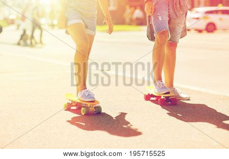 summer, extreme sport and people concept - teenage couple riding short modern cruiser skateboards on city street