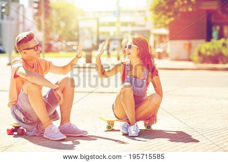 summer holidays, extreme sport, gesture and people concept - happy teenage couple with short modern cruiser skateboards on city street making high five