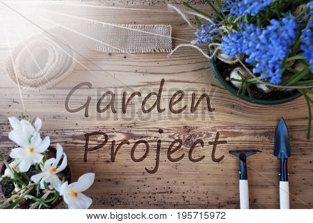 English Text Garden Project. Sunny Spring Flowers Like Grape Hyacinth And Crocus. Gardening Tools Like Rake And Shovel. Hemp Fabric Ribbon. Aged Wooden Background