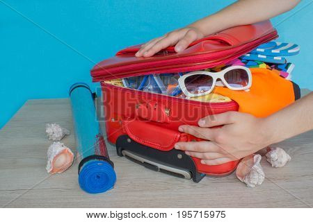 Young girl packing suitcase at home. Open suitcase packed for travelling close up