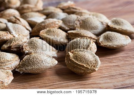 Several apricot kernels on a wooden background