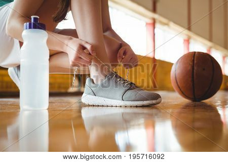 Close up of woman tying shoelace while crouching on floor in basketball court