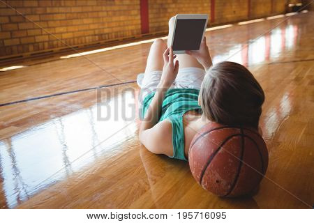 Woman using digital tablet while lying on floor in basketball court