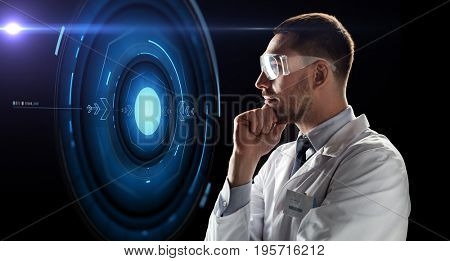technology, science, and people concept - male doctor or scientist in white coat and safety glasses looking at virtual projection over black background
