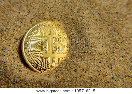 Golden bitcoin coin in the sand