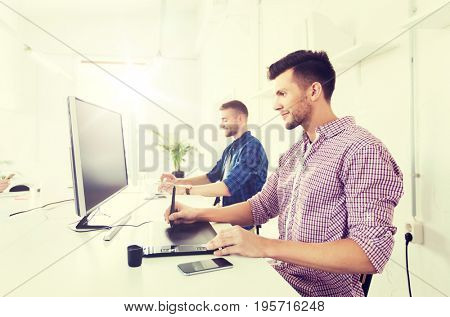business, technology, design and people concept - young creative man or designer with computer and pen tablet working at office