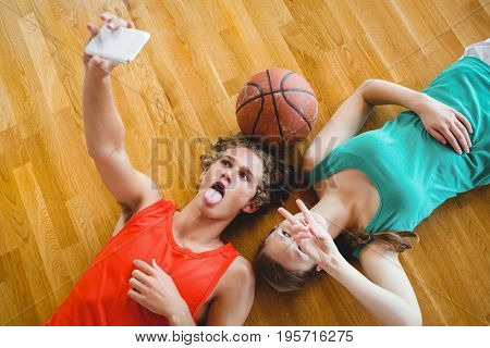 Overhead view of friends taking selfie while lying on hardwood floor in court