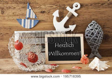 Blackboard With Nautical Summer Decoration And Wooden Background. German Text Herzlich Willkommen Means Welcome. Fish, Anchor, Shells And Fishnet For Maritime Contex.