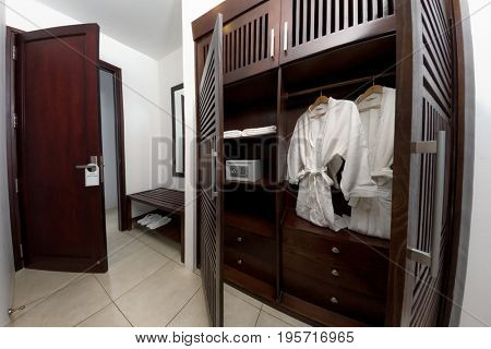 White bathrobe with wooden hangers in wardrobe. Bright and cozy hall interior design in modern urban contemporary style