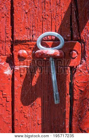 Antique iron key from a gate on a background of old red wooden gate.