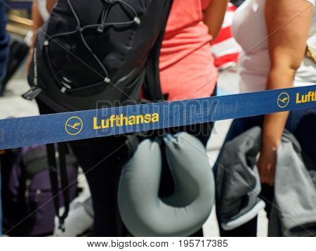 June 23 2017. Close-up detail of a Lufthansa logo on a queue barrier with people waiting for check-in in the background. Frankfurt Airport Germany. Travel and industry editorial concept.