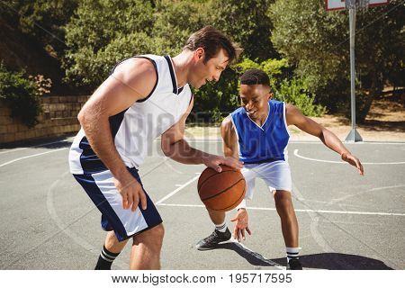 Happy friends playing basketball in court