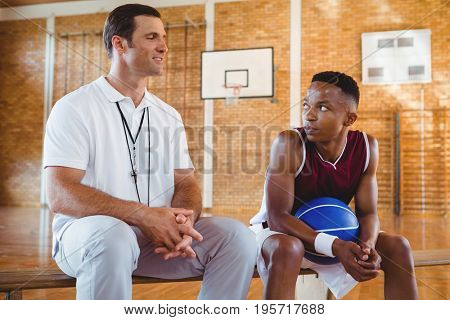 Smiling coach guiding basketball player while sitting on bench in court