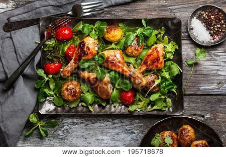 Spicy roasted chicken legs with potatoes and salad. Top view. Food in rustic style.