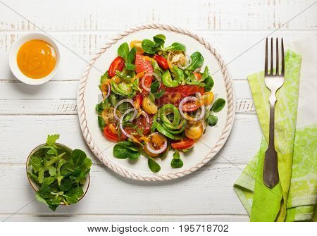 Smoked salmon, avocado and cherry tomatoes salad with honey mustard dressing.Healthy salad in plate on a wooden table. Top view