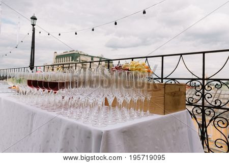 Wineglasses and fruit plate on the table outdoors for the wedding catering