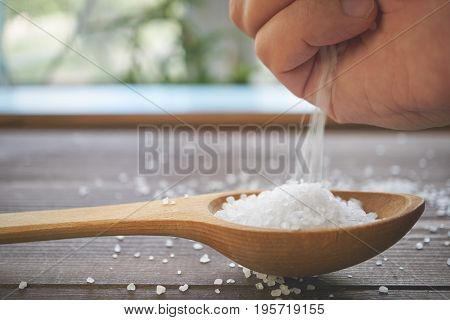 Hand With Poured Sea Salt In A Wooden Spoon On A Table, Side View
