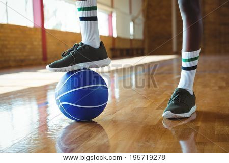 Low section of teenage boy stepping on basketball while practicing in court