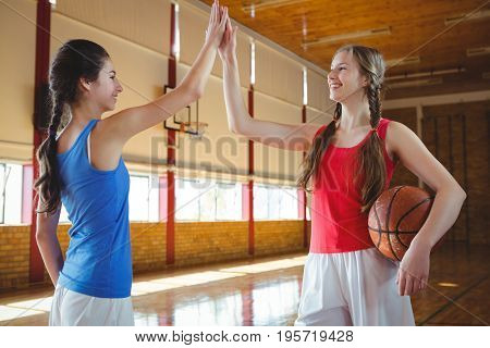 Smiling female basketball players high fiving while standing in court