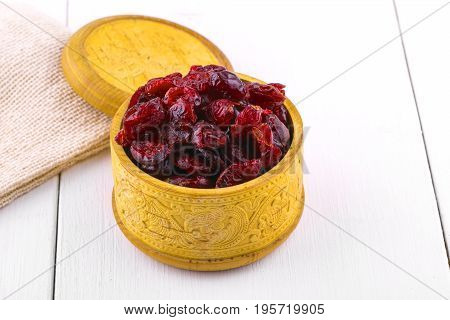 Dried cranberries in a wooden cup with a lid and burlap on a white wooden table