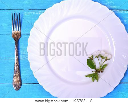 White plate with a paper sheet on a blue wooden surface with fork