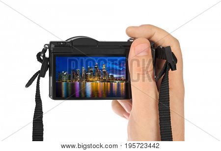 Hand with camera and Singapore city skyline (my photo) isolated on white background