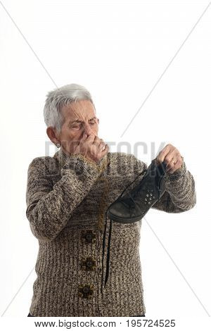 senior woman with smelling a shoe on white background